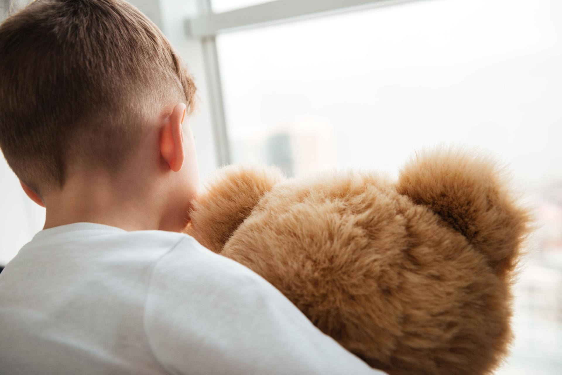 graphicstock-picture-of-alone-little-sad-boy-standing-with-teddy-bear-ne...